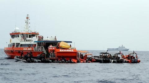 Un navire indonésien mouillant en mer entouré de canots pneumatiques.