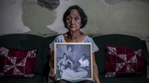 Une Indonésienne tient un portrait de ses parents entre ses mains.