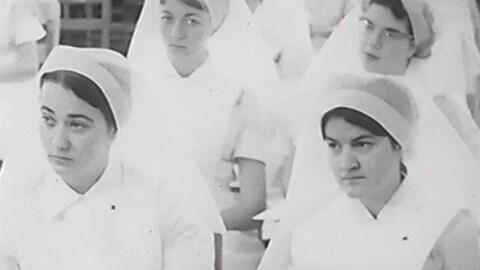 Des jeunes femmes qui portent l'uniforme (robe et voile) sont assises dans une classe.