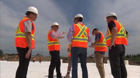 Un groupe d'ingénieurs du MTQ discutent debout sur le remblai de styromousse, sur le chantier de l'autoroute 25.