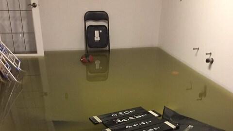 Des meubles flottent dans une pièce inondé