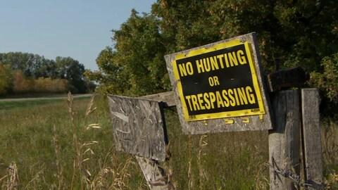 Une affiche où il est écrit en anglais qu'il est interdit de chasser ou d'être sur une terre rurale.