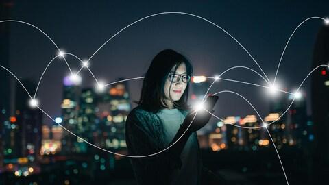 Une femme asiatique regarde son téléphone dans la pénombre avec un paysage urbain en arrière-plan. Une série de lignes courbes représentant un réseau internet parcourt la photo.