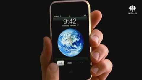 Main tenant un appareil iPhone ouvert sur l'écran d'accueil affichant l'heure et une image de planète
