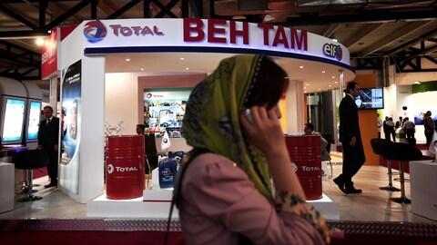 Une femme parle au téléphone en passant devant un kiosque de la pétrolière Total.