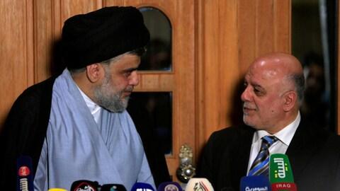 Moqtada Al-Sadr et Haïdar Al-Abadi se regardent devant les micros des médias lors d'une conférence de presse.