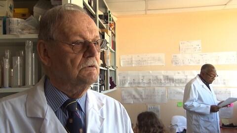 Un homme plutôt âgé portant des lunettes, en sareau blanc répond aux questions d'un journaliste qui lui est hors champ.