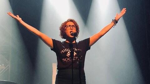 Isabelle Hébert en train de chanter au micro.