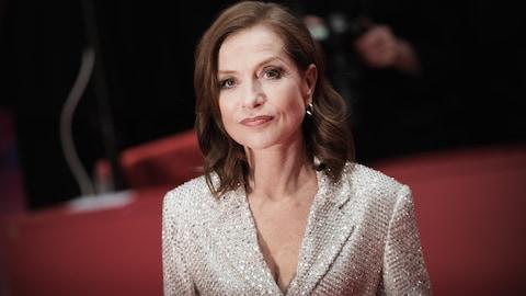 Portrait d'Isabelle Huppert, portant une veste pailletée blanche, lors de la présentation du film Eva au Festival international du film de Berlin.