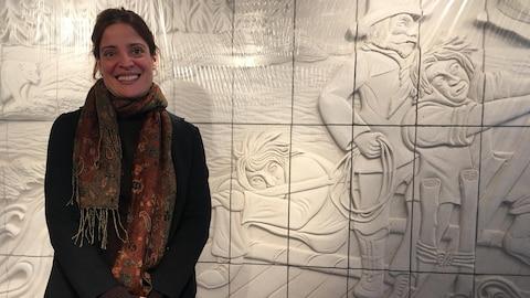 Isabelle Regout se fait prendre en photo devant son oeuvre Dompteurs d'écueil.