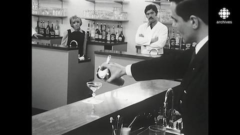 Un enseignant prépare un cocktail Gimlet à l'aide d'un shaker devant une classe d'étudiants derrière leurs bars respectifs.