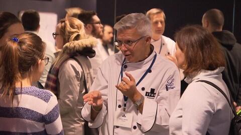 Un homme, membre de l'Institut de tourisme et d'hôtellerie du Québec, discute avec des jeunes lors des portes ouvertes de l'ITHQ.