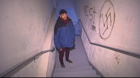 Un individu dans une cage d'escalier. Il y a des graffitis sur un mur.
