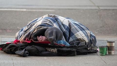 un homme qui dort dans la rue