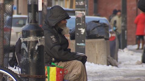Un homme récolte les dons des passants sur la rue Ontario, dans Mercier-Hochelaga-Maisonneuve