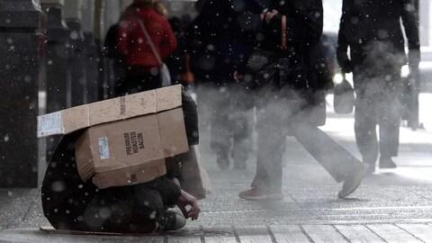 Un homme est assis sur le trottoir, courbé et avec un morceau de carton sur la tête pour se protéger des intempéries. Des passants marchent sur le trottoir sur lequel il est assis.