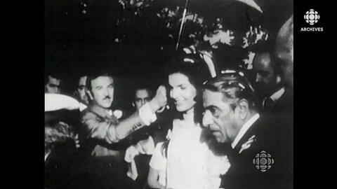Jacqueline Bouvier Kennedy et Aristote Onassis à leur sortie de la cérémonie de mariage. Un homme les couvre à l'aide d'un parapluie.
