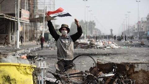 Un manifestant irakien porte le drapeau national à Najaf, ville sainte chiite du sud de l'Irak le 1er décembre 2019.