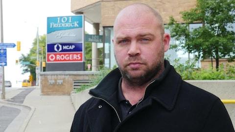 Photo d'un homme debout à l'extérieur devant une enseigne de Rogers.
