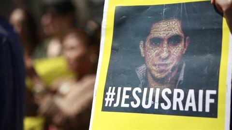 Une pancarte avec la photo de Raif Badawi et la mention « Je suis Raif ».