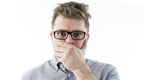 Le chroniqueur a une main sur sa bouche et semble choqué par ce qu'il voit.