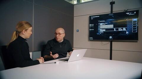 La journaliste est assise à une table avec un cadre de l'entreprise, devant un écran de télévision et un ordinateur portable.