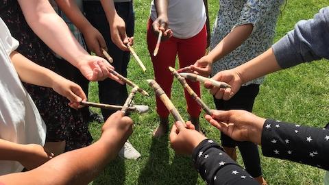 Des jeunes placés en cercle tendent vers le centre de leur ronde des bâtons taillés en pointe, sculptés et colorés.