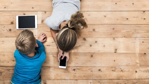Des jeunes utilisent un téléphone intelligent et une tablette.