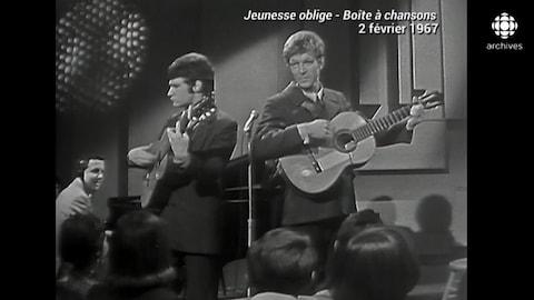 Deux musiciens jouent de la guitare, en studio.