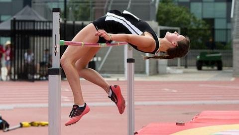 Une jeune femme aux cheveux tressés complète un saut en hauteur.