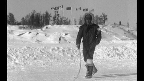 Un homme marche dans un paysage hivernale. En arrière -plan on voit un banc de neige avec des drapeaux au vent.
