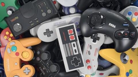 Une pile de manettes de jeux vidéo rétro dépareillées.