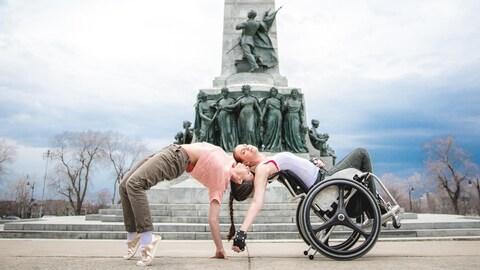 Les danseuses Joannie Douville et France Geoffroy (à droite, en fauteuil roulant) se penchent en arrière pour une chorégraphie effectuée à côté d'une colonne où se trouvent plusieurs statues.
