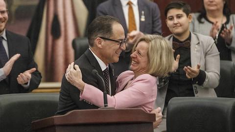 Le ministre des Finances Joe Ceci et la première ministre Rachel Notley s'enlacent après le dépôt du budget 2018.