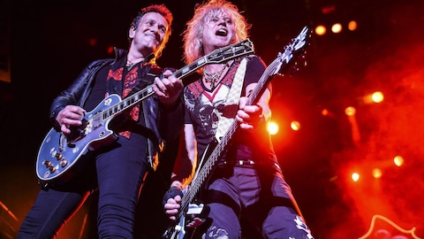 Le guitariste et le bassiste de Def Leppard, sur scène, sourient en regardant la foule.