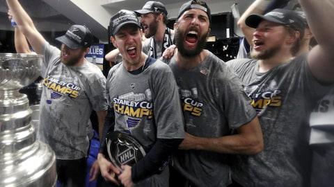 Des joueurs de hockey fêtent leur victoire. La photo montre cinq joueurs portant des t-shirts sur lesquels on peut lire en anglais les mots « Stanley Cup Champions ». Ils fêtent et versent de la bière dans la coupe Stanley.