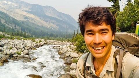 Photo de John Chau devant un ruisseau et une montagne.