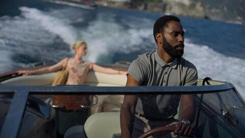 Un homme est aux commandes d'un bateau.