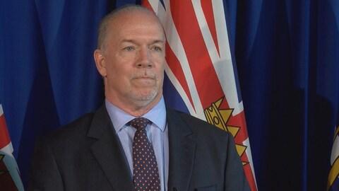 Le premier ministre John Horgan devant un drapeau de la Colombie-Britannique lors d'un point de presse le 8 août 2017