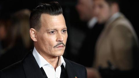 L'acteur Johnny Depp regarde au loin, alors qu'il prend la pose sur un tapis rouge, lors de la première d'un film.