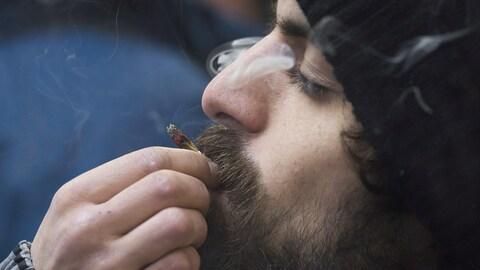 Un homme fume un joint.