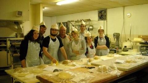 Un groupe de jeunes devant une table de pain.