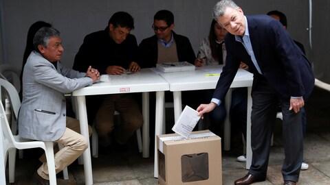L'homme en costume met son bulletin dans une urne en carton