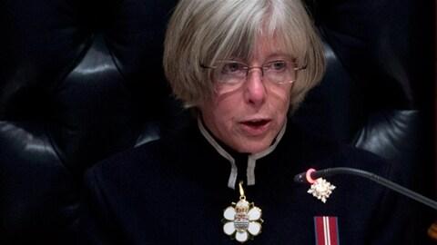 Une femme aux cheveux gris courts porte des lunettes et un habit marin et parle au micro.