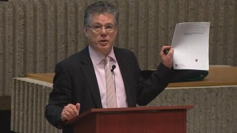 Le juge Richard Chartier est debout à un lutrin et brandit un document sur lequel on peut lire L'accès à la justice en matière civile et famliale.