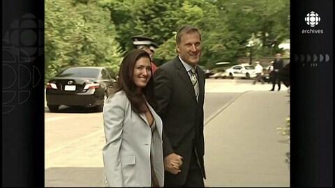 Maxime Bernier et Julie Couillard marchant main dans la main et souriant à la caméra