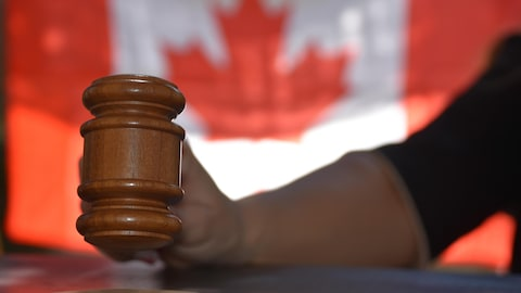 Gros plan sur le maillet d'une juge et drapeau du Canada en arrière-plan.