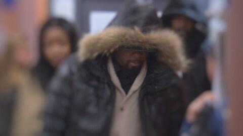 Samuel Jacques, vêtu d'un manteau qui lui recouvre les yeux.