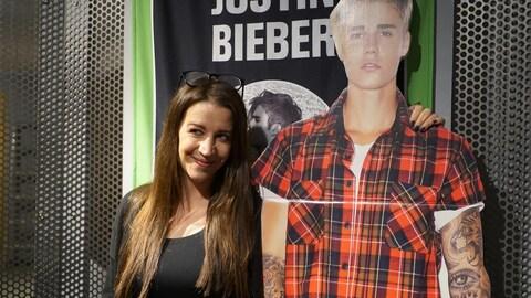 Photo d'une femme qui tient par l'épaule une doublure en carton de Justin Bieber portant une chemise à carreaux.