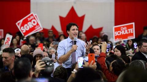 Justin Trudeau parle au micro au milieu d'une foule. Derrière lui se trouve un immense drapeau du Canada.